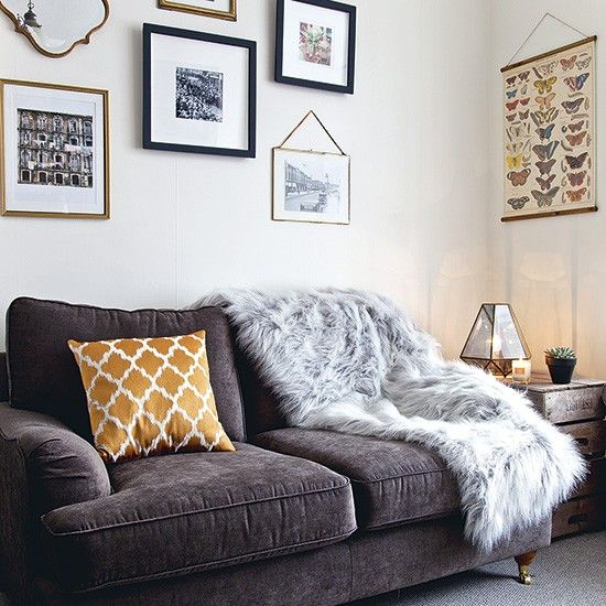Neutral modern living room with faux-fur throw and wall display ...