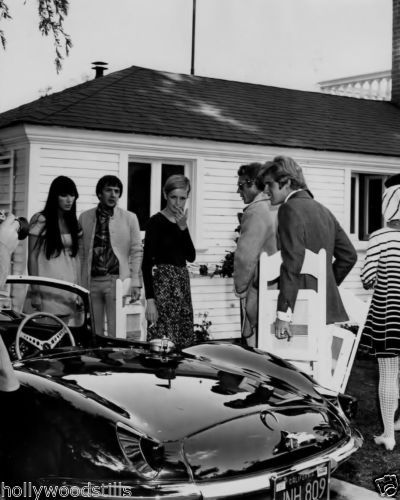 Steve McQueen shows Sonny Cher and Twiggy his Jaguar car. Rare movie star 8x10 photo. Great gift idea for car and / or celebrity buffs.