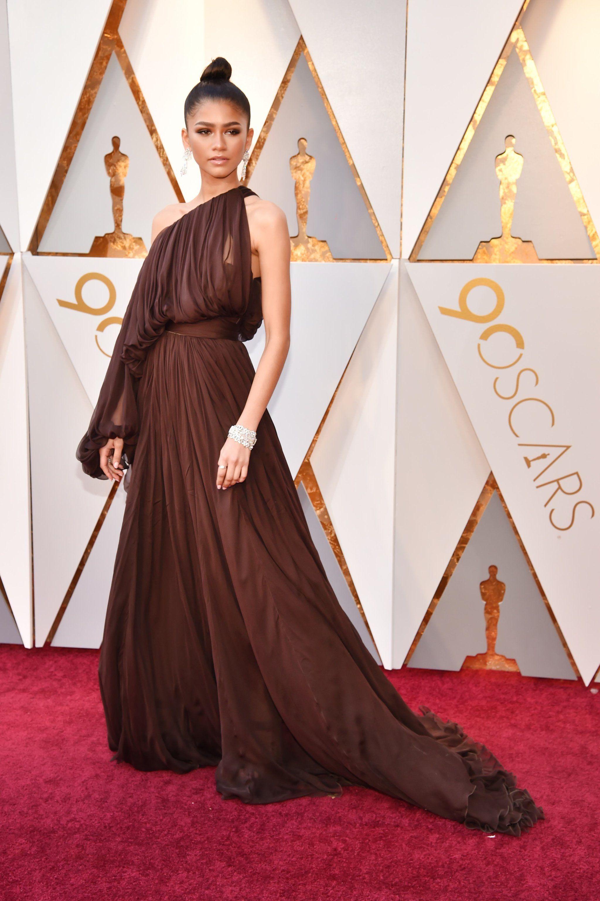 Zendayaus dress looks like itus falling off her shoulder but donut