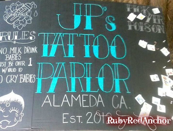 I created this sign for a rock theme first birthday party. It came out better than I had hoped! I'm thinking of making a more permanent for my son. I made it free hand on a black science board & used silver Sharpie & blue glitter glue. #rockstar #firstbirthday #temporarytattoo parlor