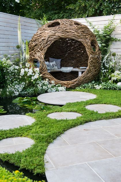 woven willow bird hide (willow sculpture) and concrete circular slabs as a path…