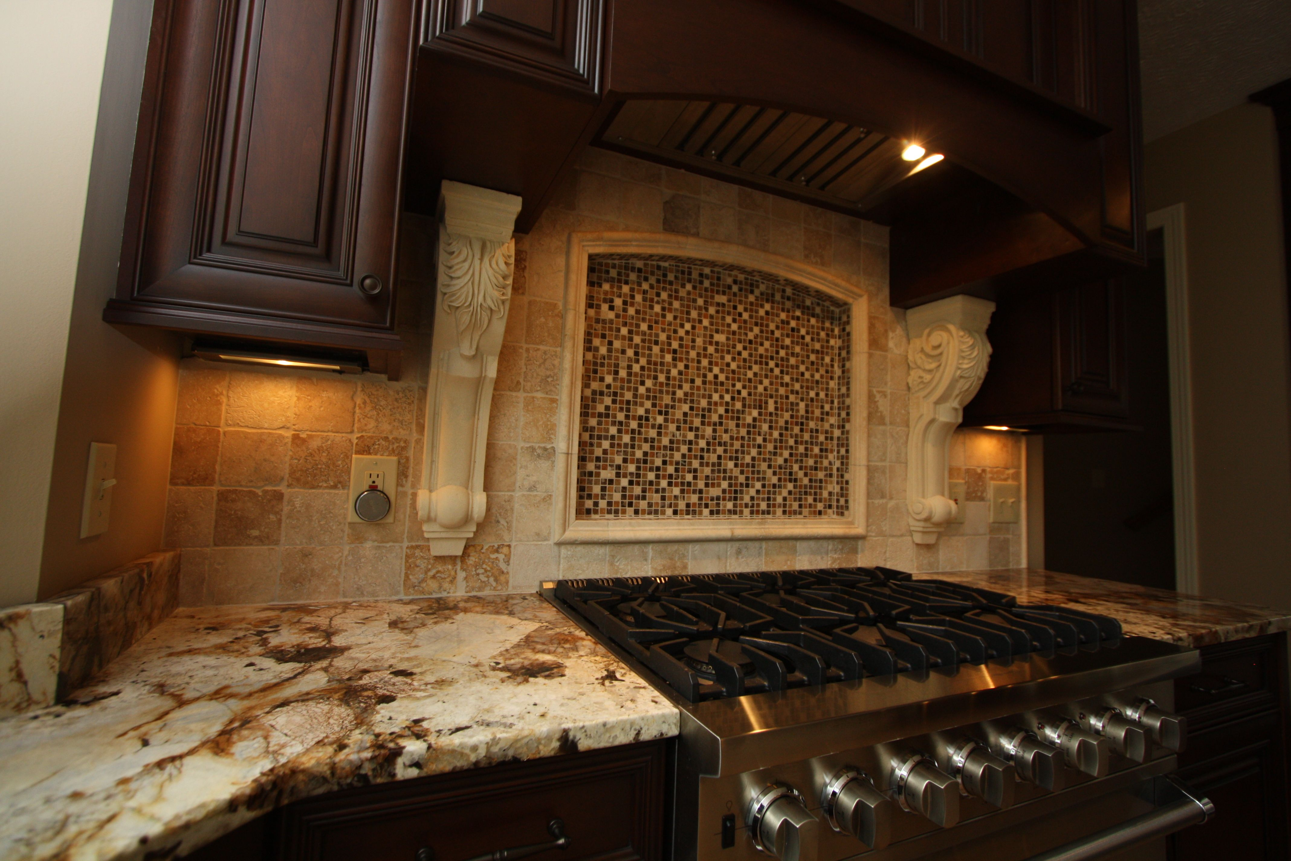 custom mosaic tile backsplash with cast stone corbels
