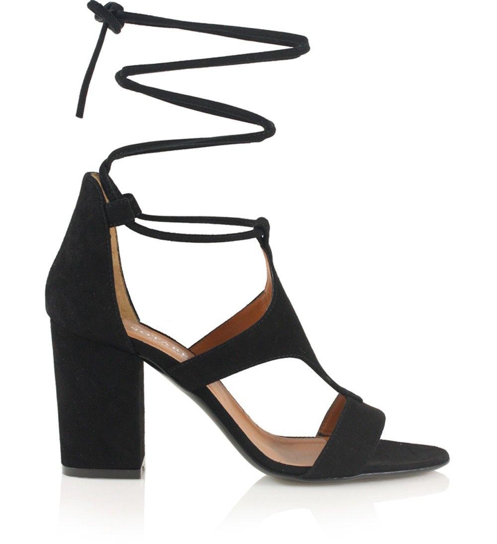 Sort strappy ruskindssandal med snører til binding om anklen og smukke udskæringsdetaljer på forfoden.