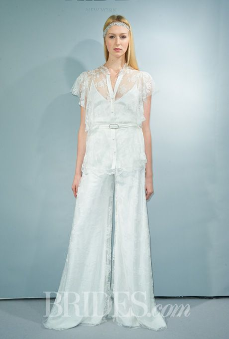 6e5f801d6c Brides.com  Victoria Kyriakides - Fall 2014. Lace and silk satin wedding  jumpsuit with a sheer v-neckline and flutter short sleeves