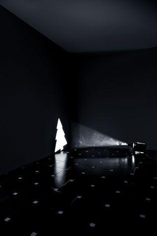 Luci di Natale: illuminazione delle feste addobbi. Un faretto e un foglio di alluminio o di un materiale non infiammabile dove proiettare l'ombra di una mascherina con la sagoma di un abete. Un angolo di casa deliziosamente chic.