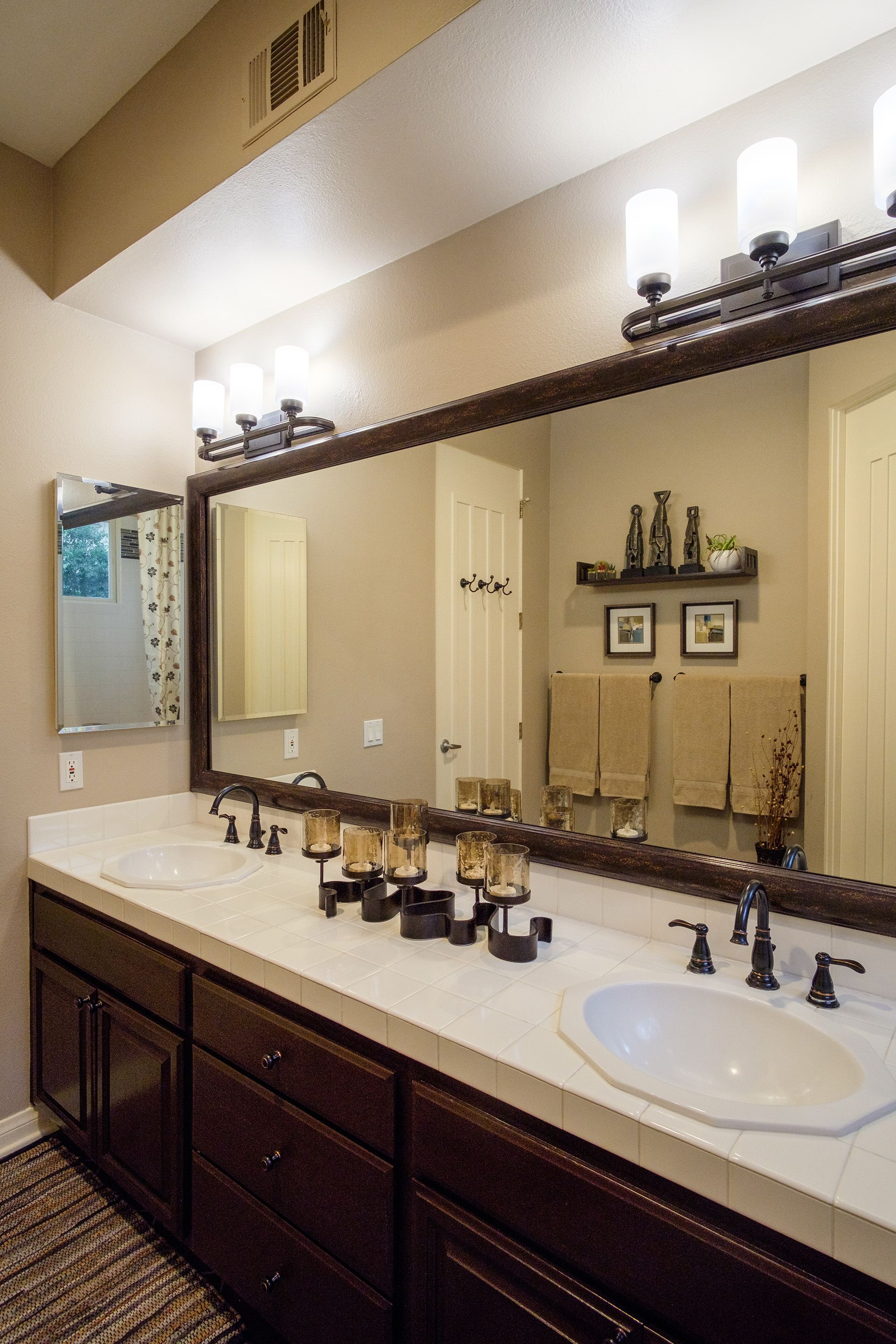 Visually Enlarge And Freshen A Dated Bathroom With Wood Tone Mirror
