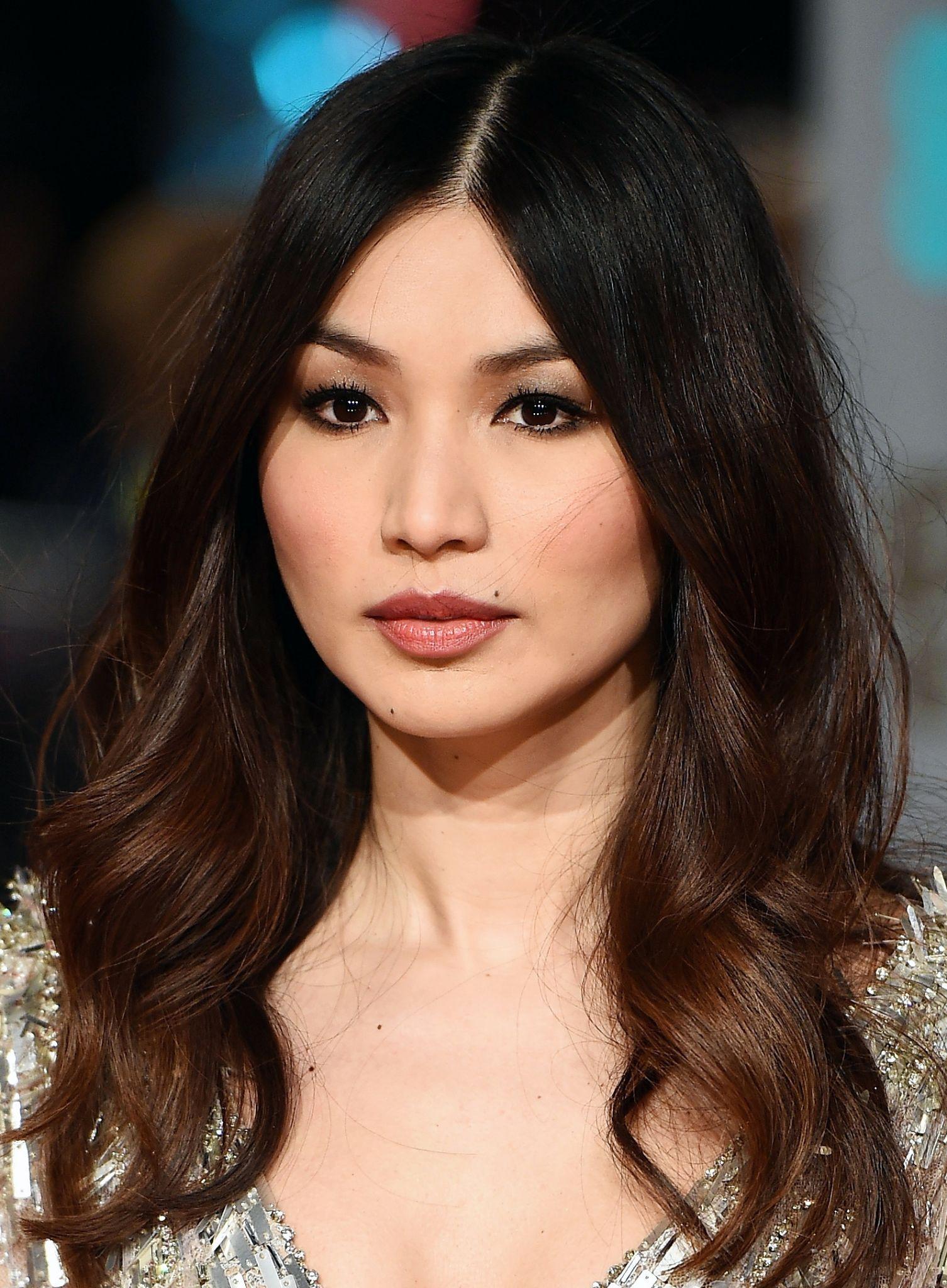 Gemma Chan super gata com o cabelo ondas suaves e risca milimétrica no meio + make com pele de boneca, blush mais marcado e olho esfumado com tons de cinza e preto no contorno