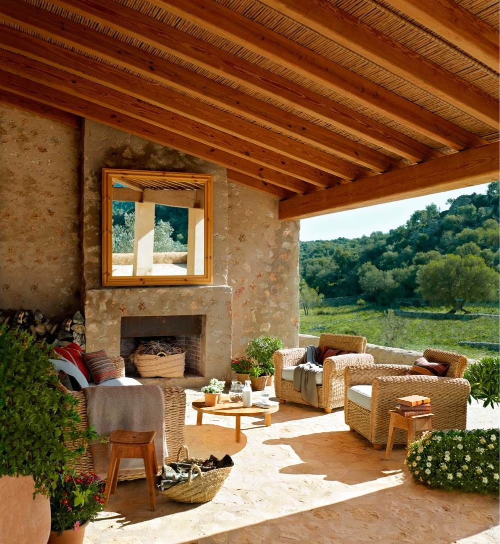 Porche con chimenea pared de piedra sillones y sof s de - Casas con porche ...