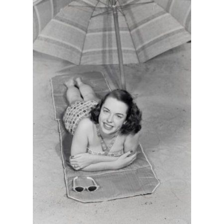 Young woman lying under beach umbrella Canvas Art - (18 x 24)