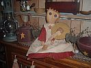 Rustina Bell Rustina Belle is new to our Primitive doll family.  She is approximately 24 inches tall with rusty bells attached to her head (which looks like hair rollers to me). She is made of stained muslin with a stitched nose and mouth. The outer layer of her dress is of stained muslin which covers colored fabric. Her eyes are large buttons and she comes with a rusty star necklace.  Beauty is in the eye of the beholder on this one.   Note: Color of the under dress may vary due to availabilit #airfreshnerdolls