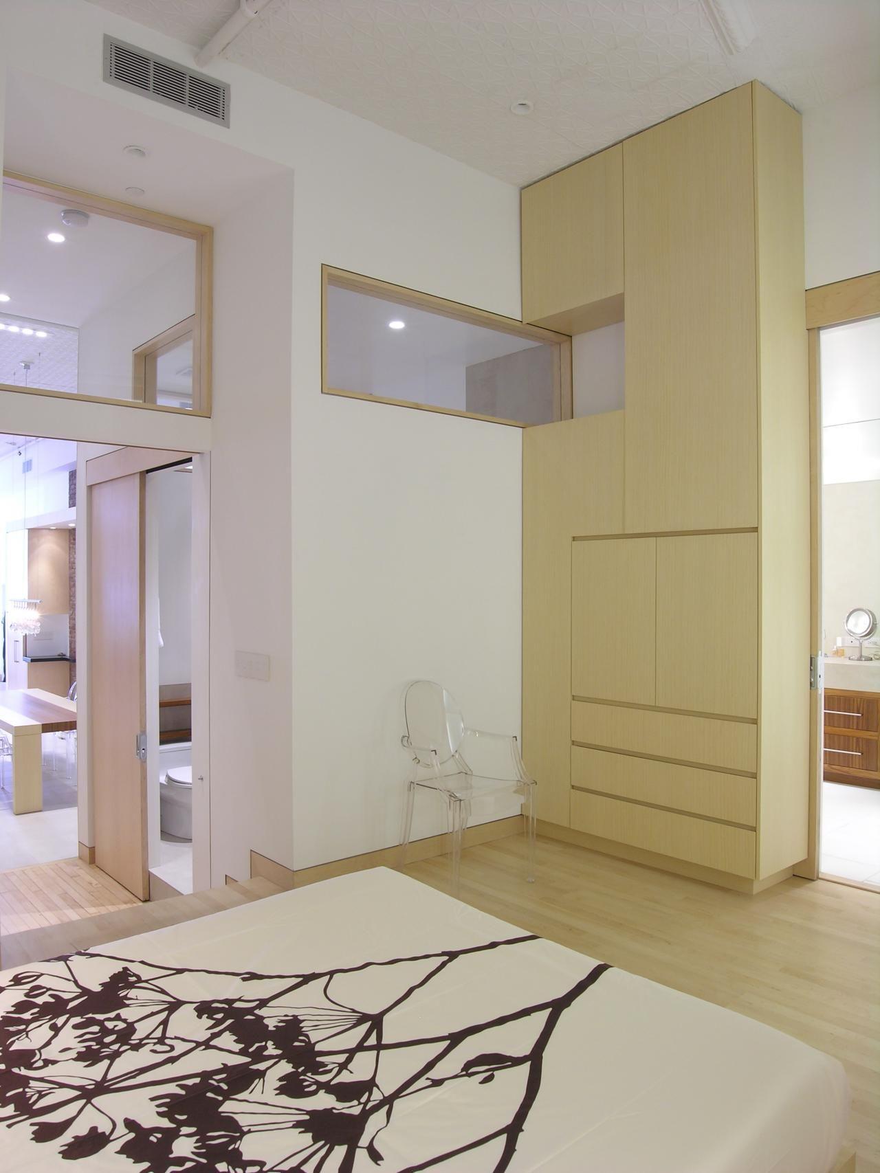 Master bedroom hardwood floors  This minimalistic white master bedroom features a floortoceiling