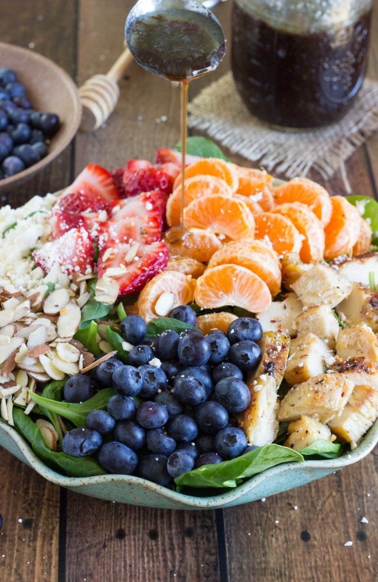 A healthy and incredibly simple spinach salad topped with chicken breast, strawberries, blueberries, toasted almonds, feta cheese, clementines, a squeeze of lemon, and a balsamic vinegar dressing. …