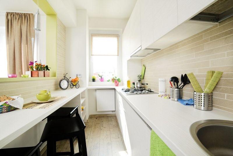 schmale Küche mit weißen Schrankfronten, Fliesenspiegel in Sandfarbe ...