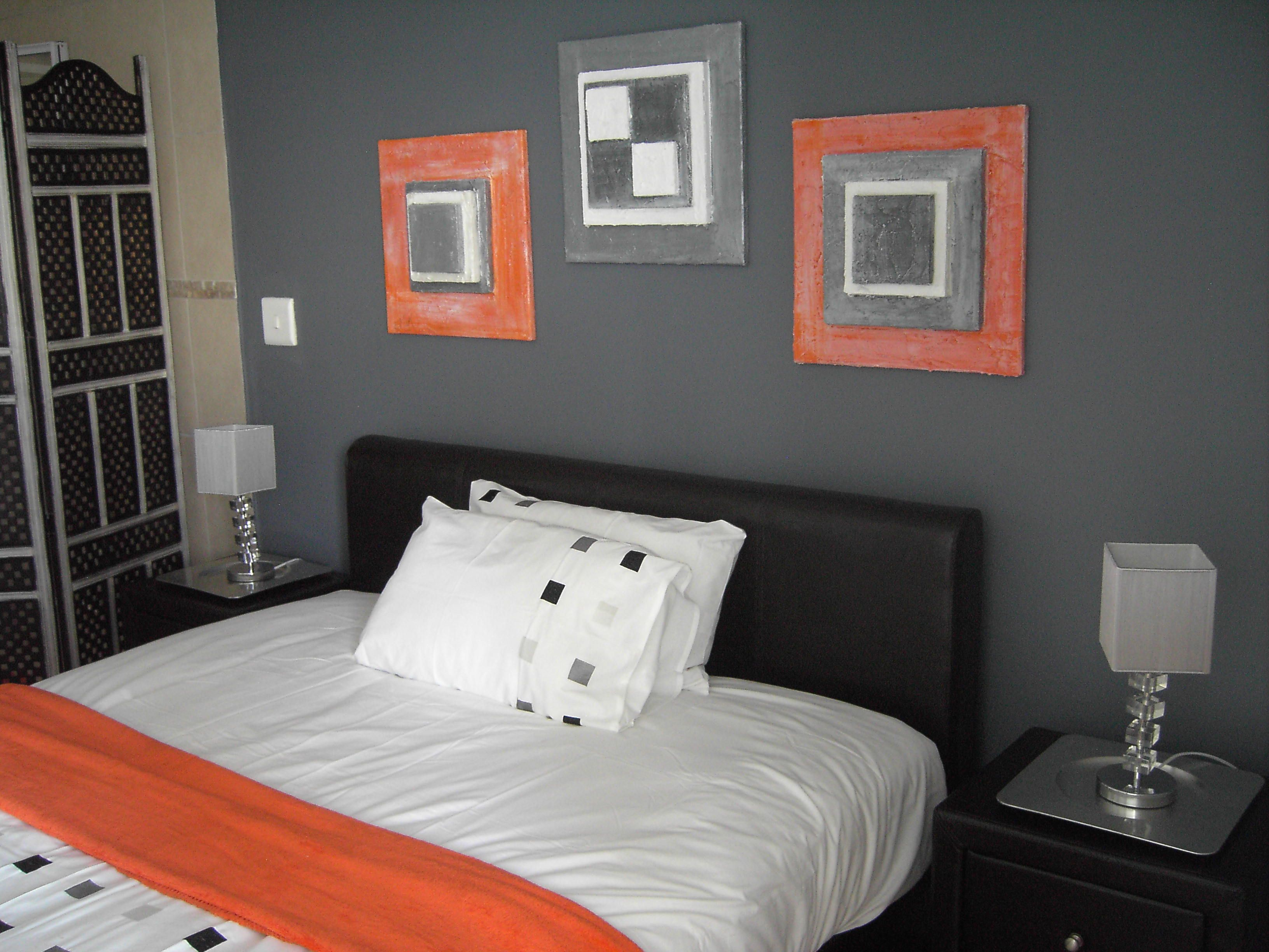 orange and grey bedroom. Love the colors. Especially like the artwork and  use of