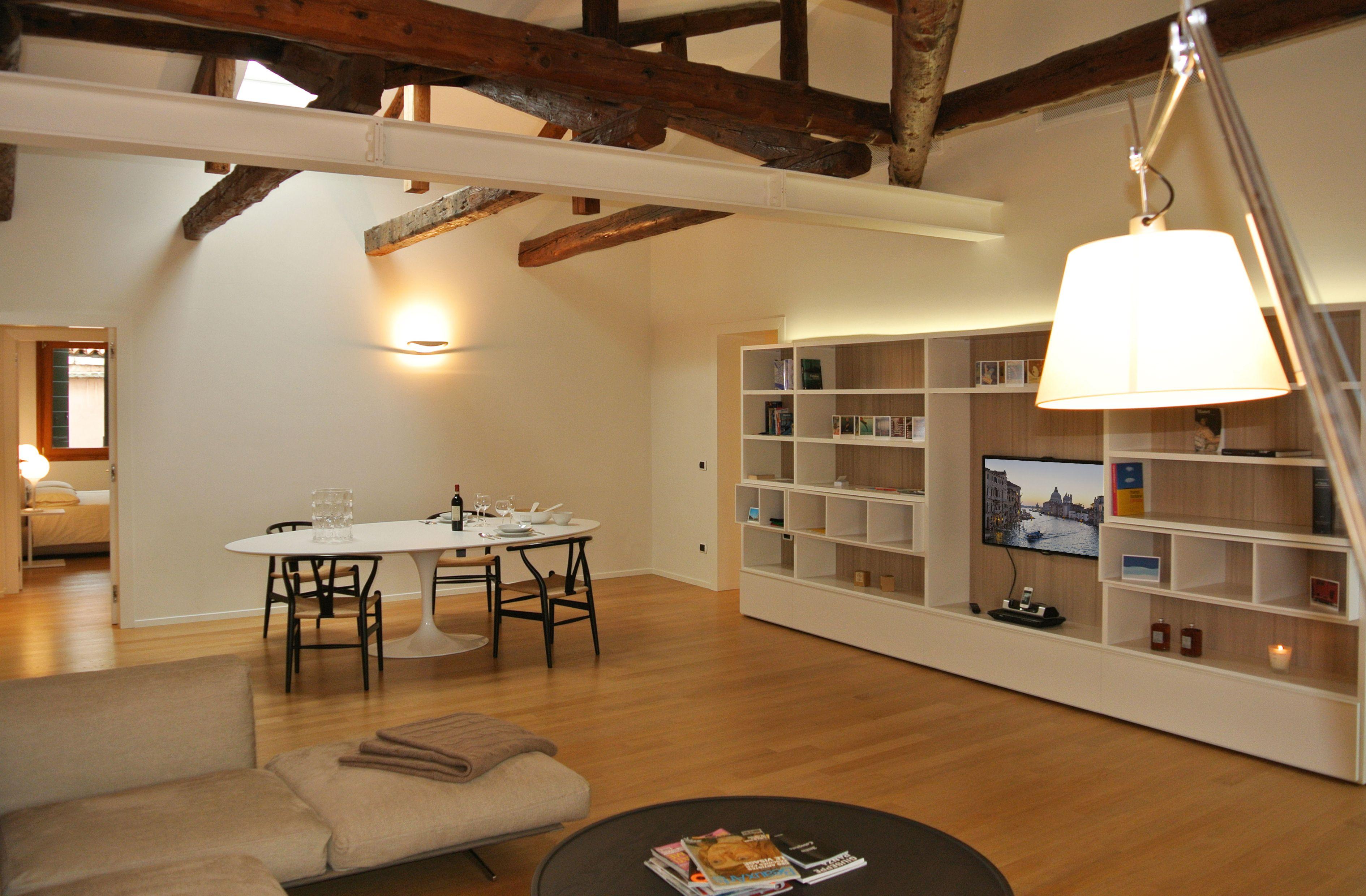 Vista sull\'ampio soggiorno, con zona pranzo, libreria e divano ...