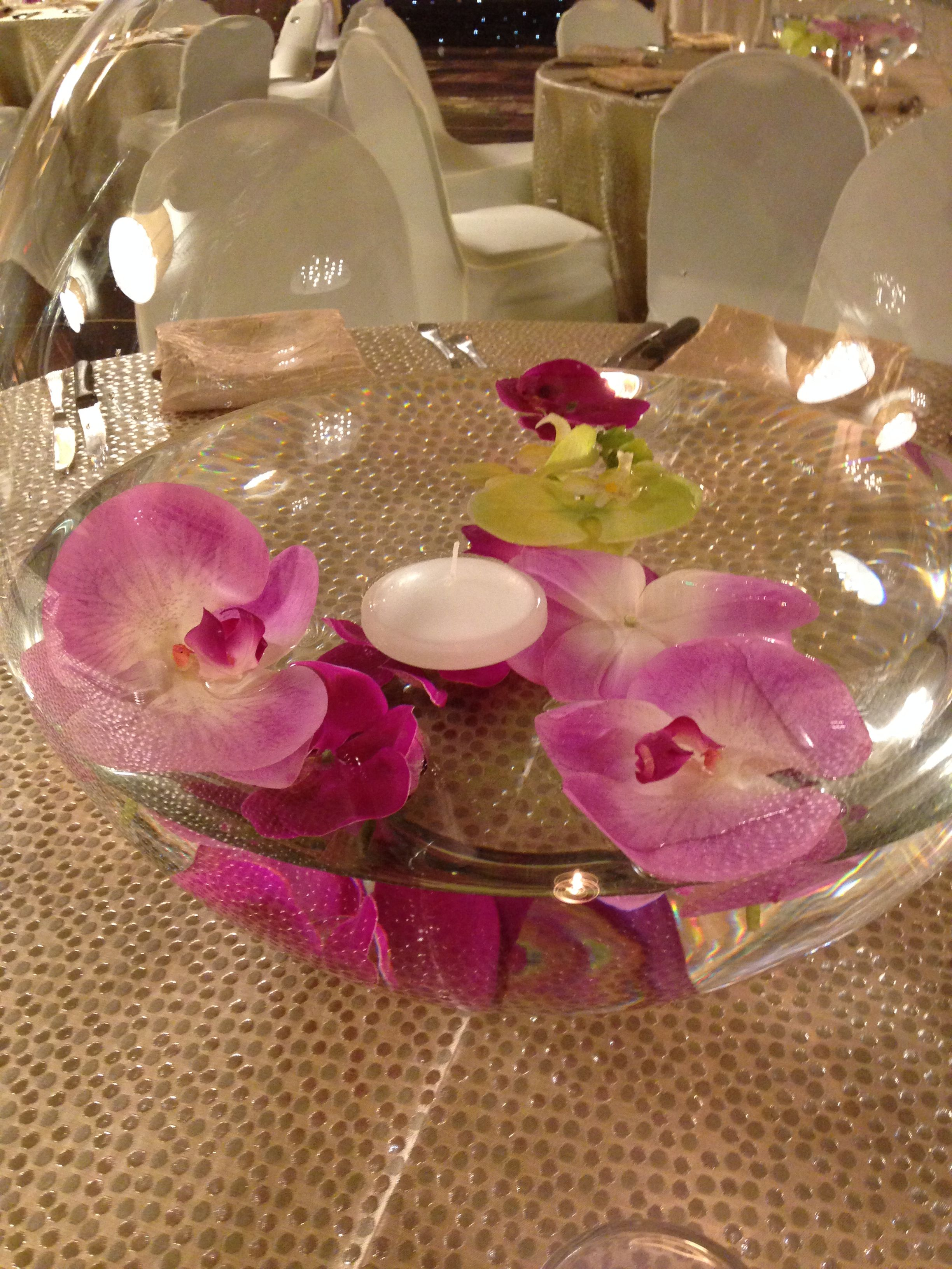floating flowers and candles in a giant fish bowl is a simple way to ...