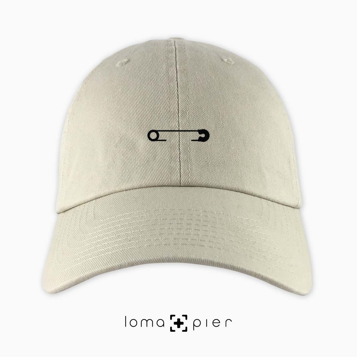 Safety Pin Icon Embroidered On A Khaki Unstructured Dad Hat With Black  Thread By Loma+