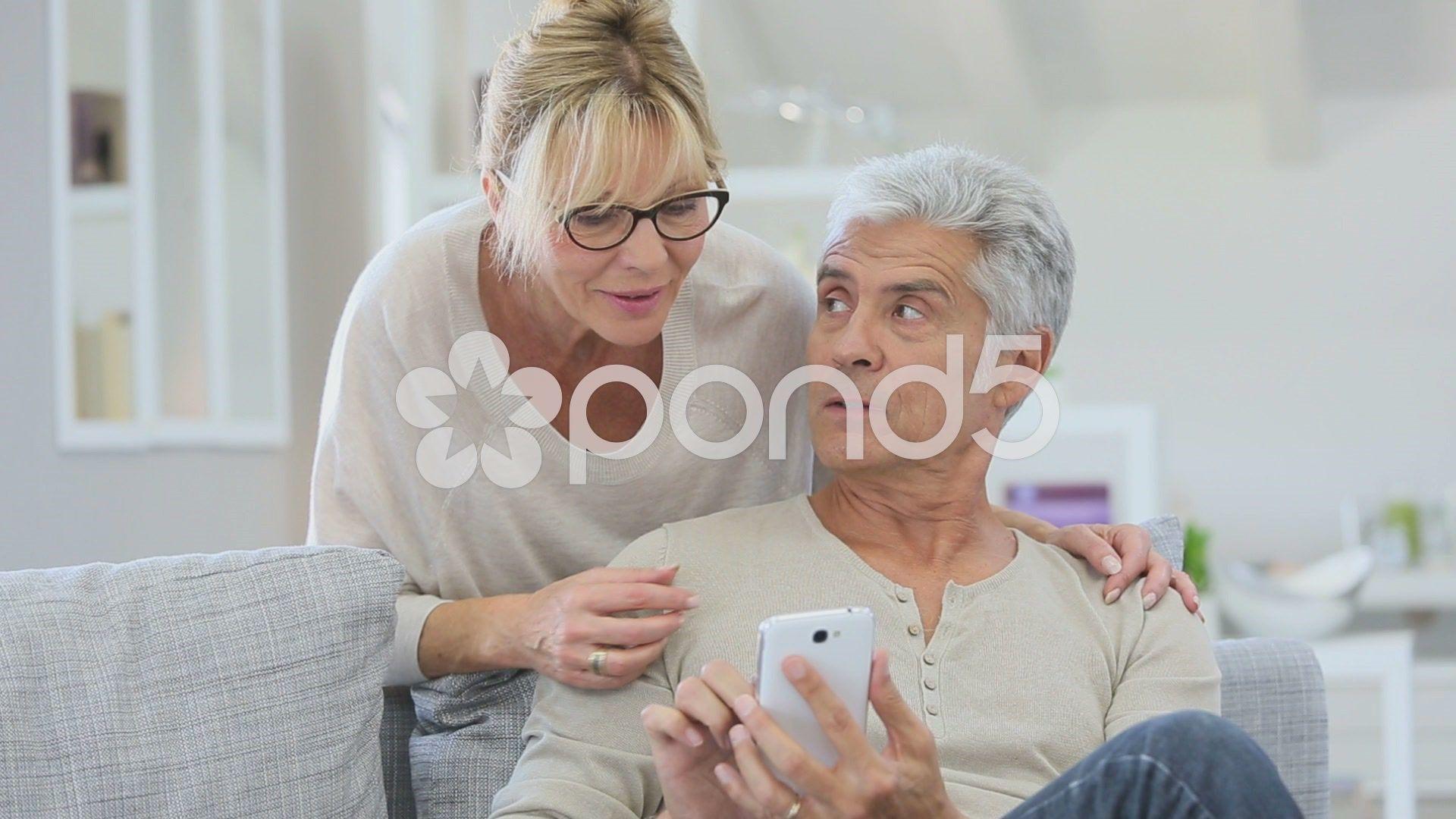 Senior couple looking at message on smartphone Stock Footage messagecoupleFootageSenior