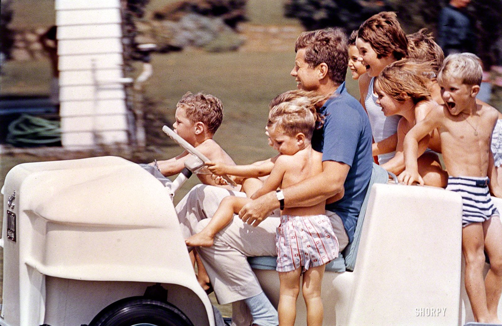 "Uncle Jack: 1961 - August 1961. Summer in Hyannis Port: ""President John F. Kennedy driving a golf cart full of Kennedy [Shriver, Smith, Lawford] family children."" Photo by Stanley Tretick for the Look magazine assignment ""Uncle Jack."""