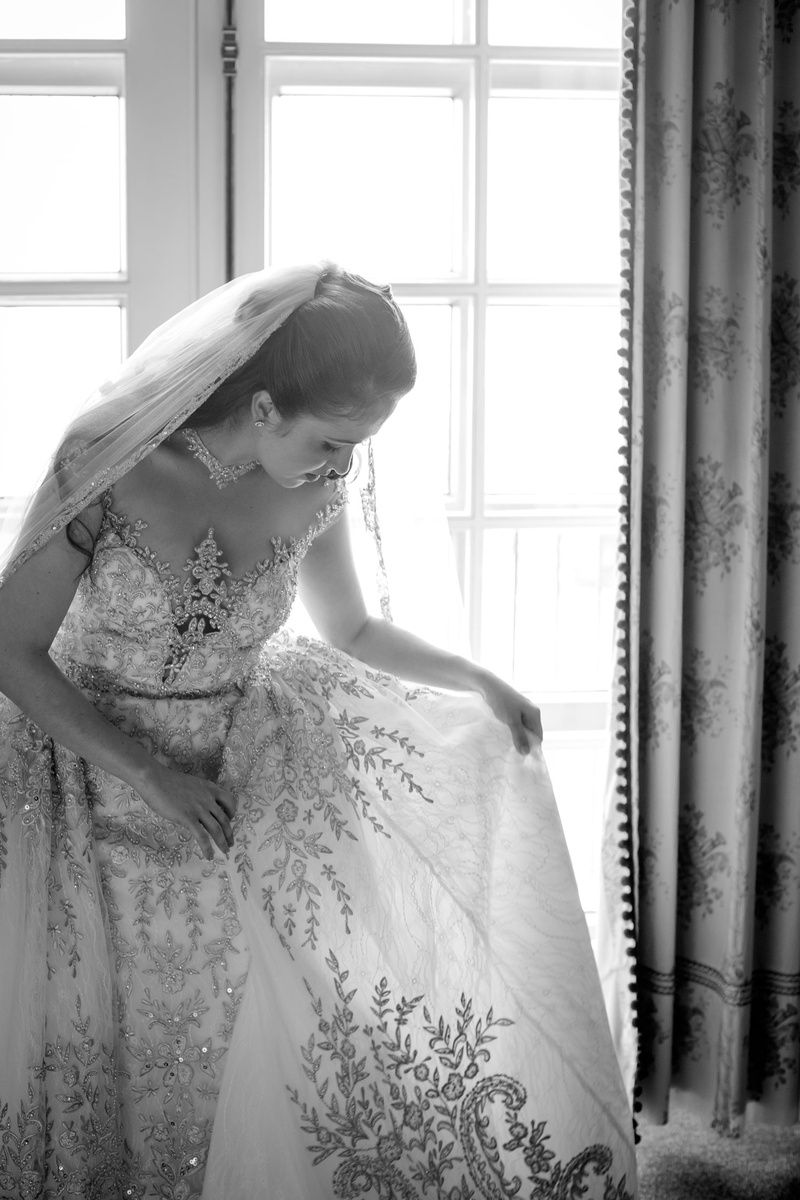 Black and White Photo of bride looking at detail of