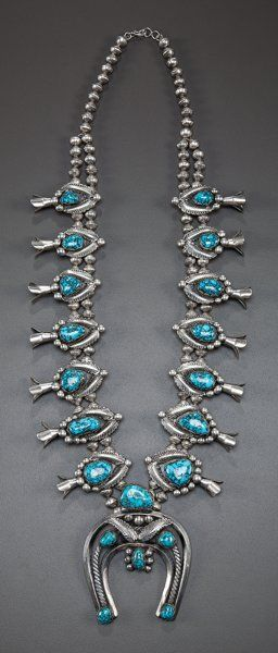 A NAVAJO SILVER AND TURQUOISE SQUASH BLOSSOM NECKLACE...