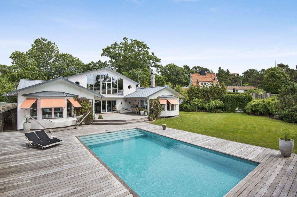 Un beau bassin rectangulaire au milieu du bois. Le bleu de la #piscine s'accorde très esthétiquement avec la plage en bois vieilli et la façade blanche de la maison. @vivremapiscine