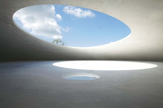 Artist Rei Naito and architect Ryue Nishizawa,Teshima Art Museum at the Benesse Art Site. It embodies creator Soichiro Fukutake's ideal of harmonizing art and nature, starting with Naoshima. on neighboring Teshima island, gleaming white concrete grotto harks back to a more primitive way of dwelling—two oval openings in the ceiling allow light, wind and rain into the building, gently coaxing visitors into direct communion with the elements.