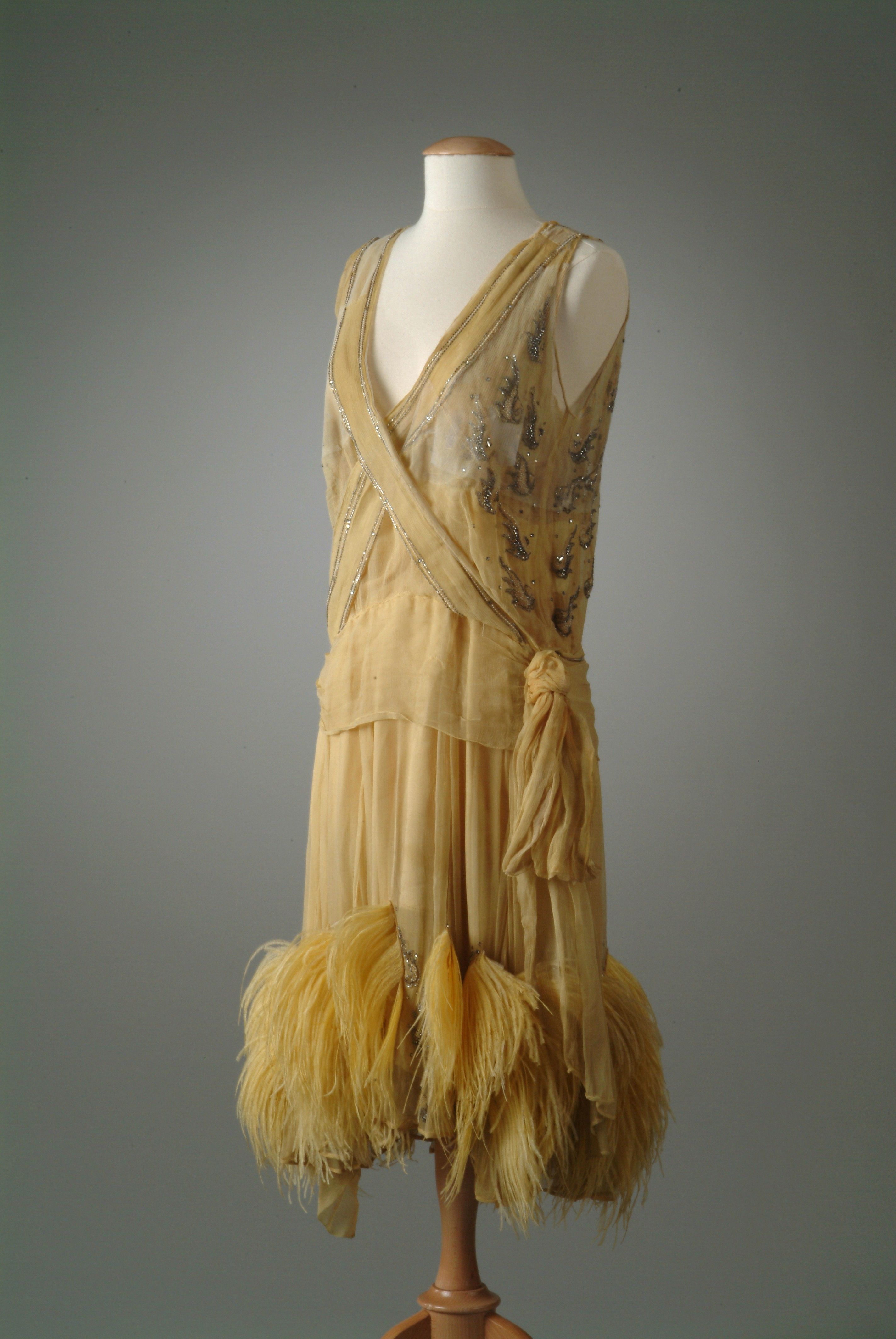 Evening gown (front)   1927   Saffron yellow silk chiffon. A criss-cross effect on the bodice is achieved with edging of rhinestones and seed pearls. Gussets on the skirt are accented with yellow ostrich feathers and beads.   Meadow Brook Hall Historic Costume Collection