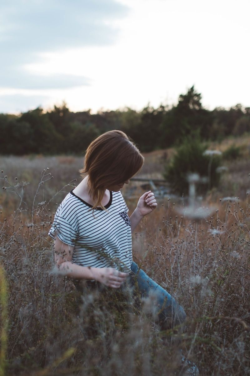 New free photo from Pexels: https://www.pexels.com/photo/woman-in-black-and-white-stripes-printed-shirt-and-blue-denim-jeans-in-brown-plant-field-under-cloudy-sky-25769/ #woman #girl #grass