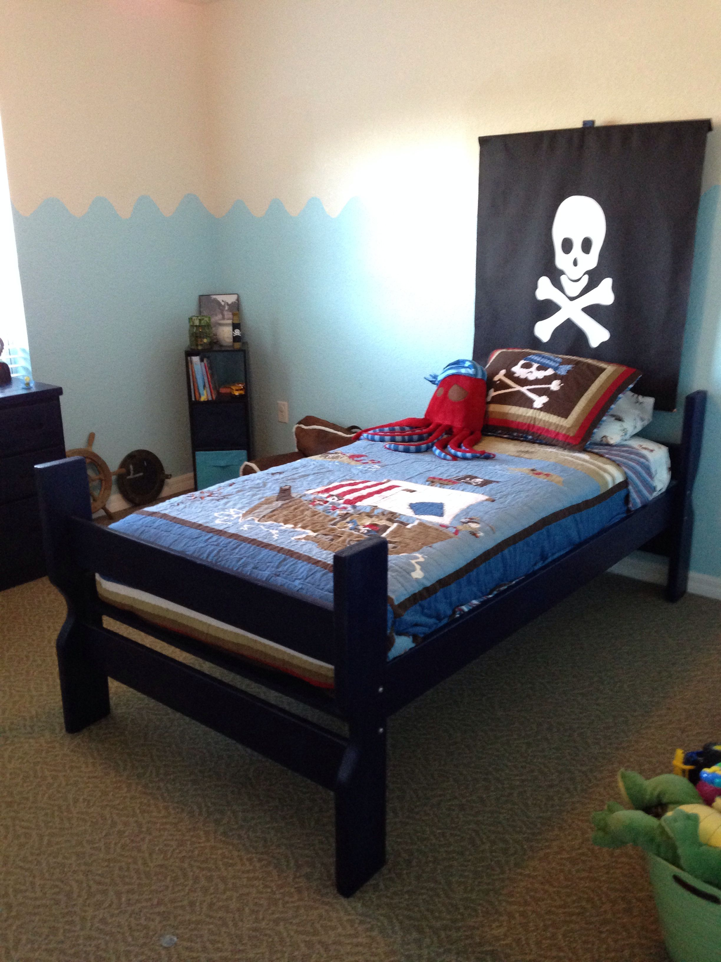DIY pirate flag bed- skull & crossbones wall decal, a $5 piece if fabric and two wooden dowels. Just place decal on fabric and sew the top and bottom just enough that the dowels will go through. Then nail it to a long piece of wood, that you can screw into the back of the bed!