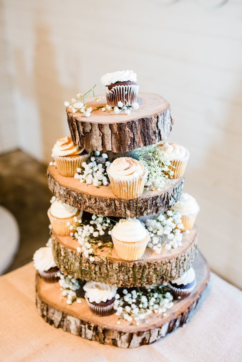 A Red Barn Wedding in Arkansas for High School Sweethearts Mini wedding cupcakes on wood cupcake tower with baby's breath at a rustic fall barn wedding reception.