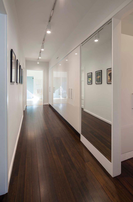 Hallway storage with sliding doors  Professorus Row Renovation by aamodt  plumb architects