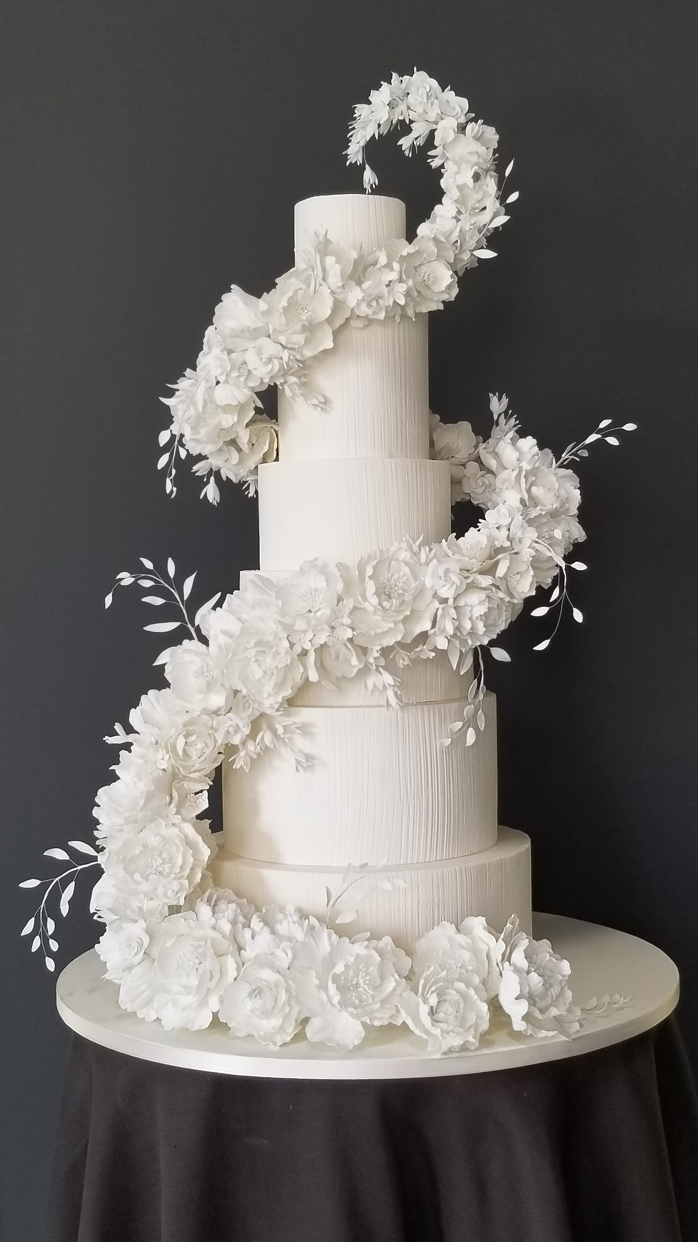 All white wedding cake with cascading white sugar flowers made with ChocoPan by Satin Ice Covering