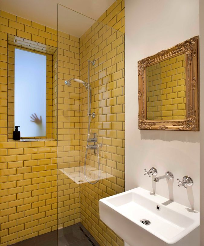 Yellow tile in shower, gold mirror