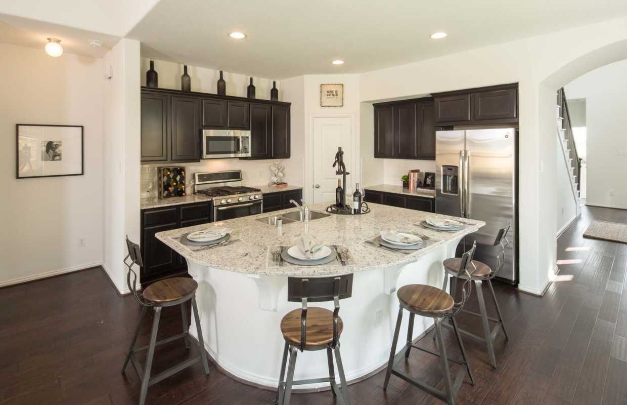 A uniquely shaped kitchen island provides both style and function ...