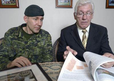 Reverend Harold Ristau, 40, and his father, Willi Ristau, 76, browse through Willi's self published book on their family history. The pair reflected on how they have been affect by war.