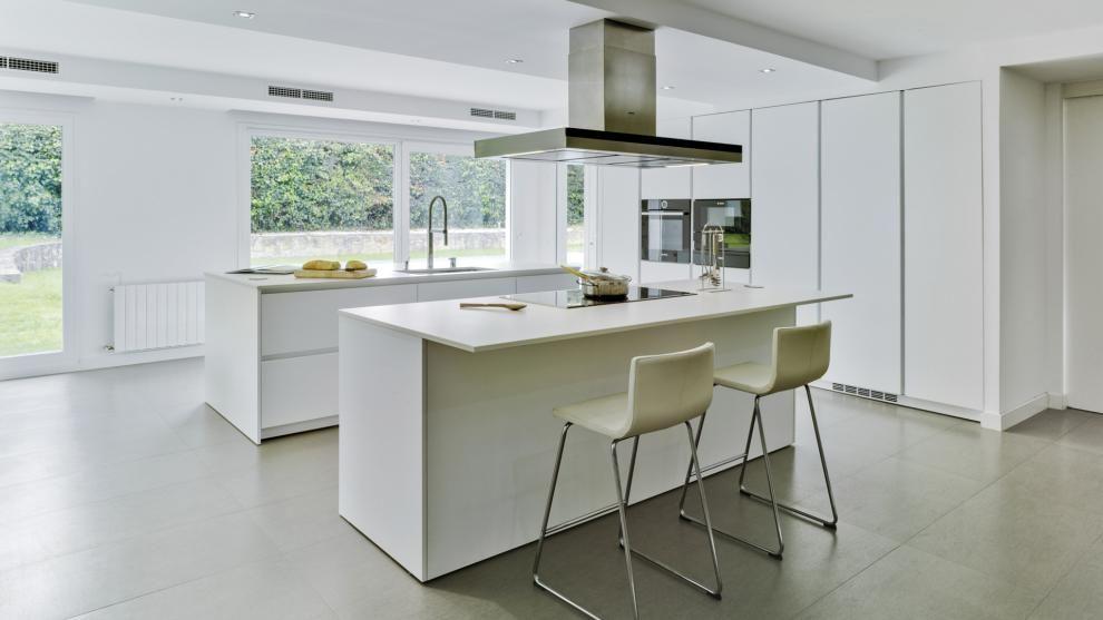 Cocina blanca con isla abierta al comedor amueblada con el for Disenos de islas para cocinas