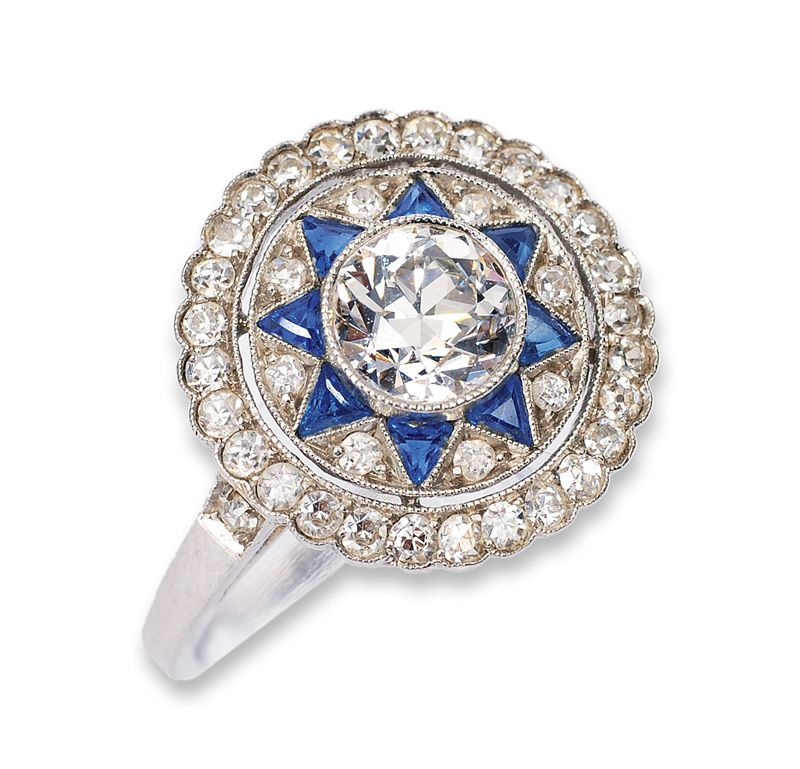 An Art-déco diamond ring with small sapphires  C. 1920. 18 ct. white gold. In the center one old cut single stone of fine quality c. 0,60 ct., framed by 38 small diam. and 8 sapphires in triangle cut. Diam. in total c. 0,95 ct. W-TCrys.vvsi-si/P. Size c. 53.
