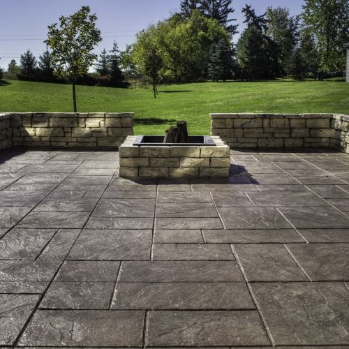 Enhance A Stamped Concrete Patio With A Fire Pit And Seat