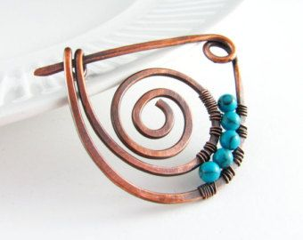 Copper Shawl Pin Scarf or Sweater Pin Fibula Wire Wrapped Jewelry Hammered Copper Brooch Copper Wire Wrap This beautiful pin is made of solid copper that has been hand forged and hammered for strength. Accented with wire wrapping and a glass bead pretty shades of turquoise and gold. The pin has been oxidized and protected with a hand buffed polish. It is suitable for both knits and looser woven fabrics. Each pin is handmade and hand forged, therefore although I give great attention to make…