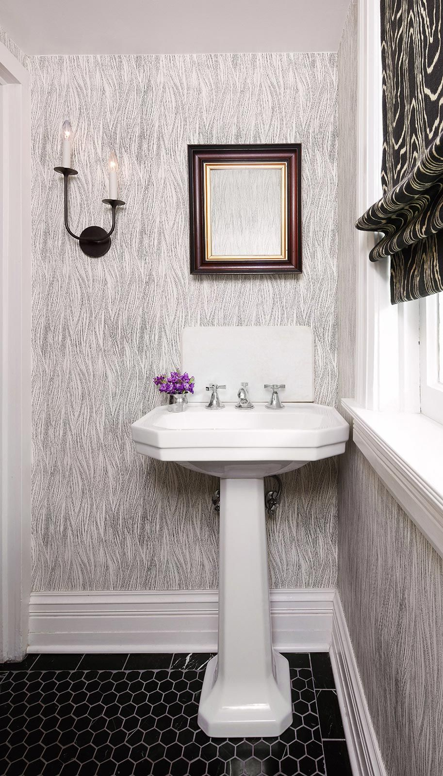 Grey and white wallpaper design and black tiled floor in powder room ...
