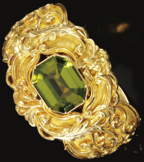 The hinged bangle centring on an octagonal step-cut peridot, to a repoussé work frame and bangle with acanthus leaves and scroll motifs, mounted in gold, inner circumference approximately 150mm, fitted case, central jewel detachable may be worn as a pendant, pendant loop.