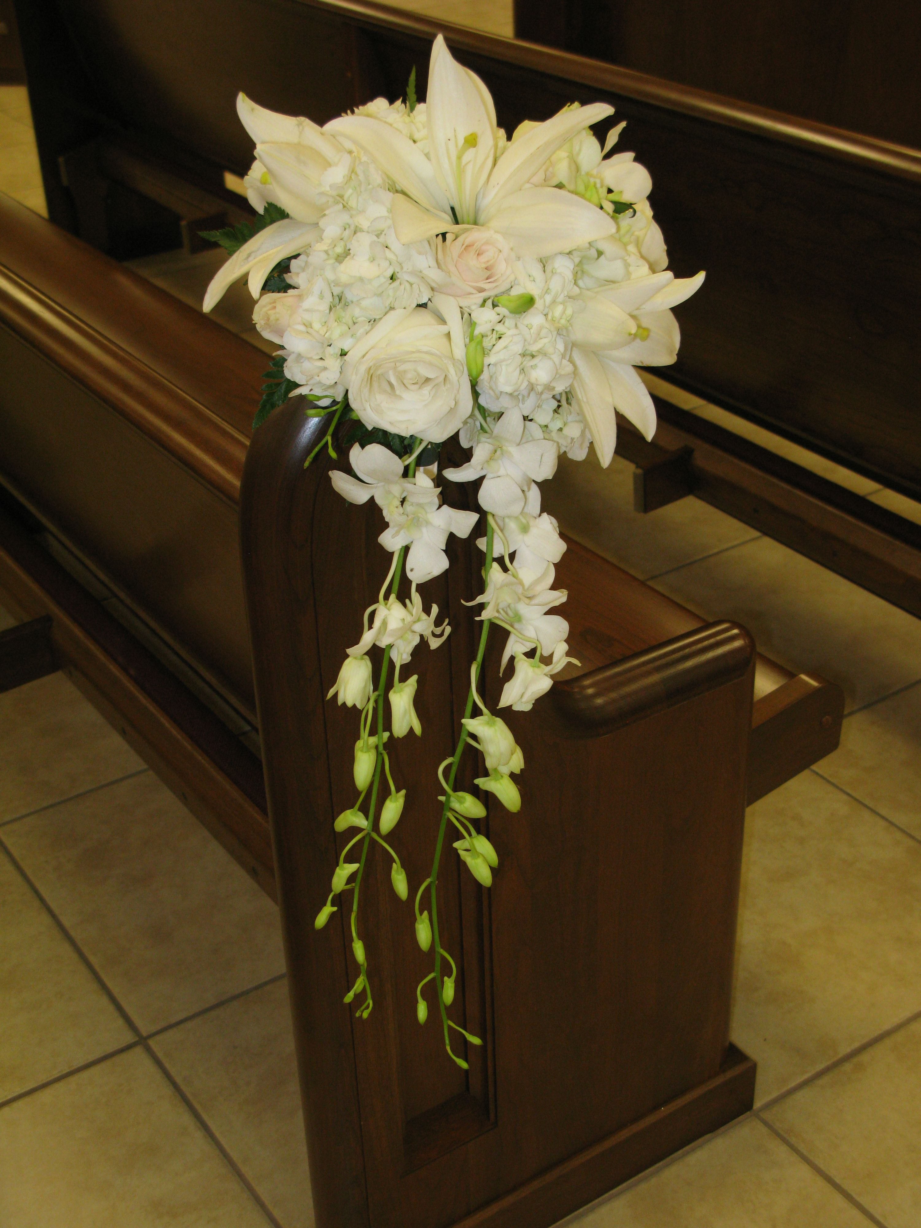 Fresh cascade pew marker arrangement. Honey wedding