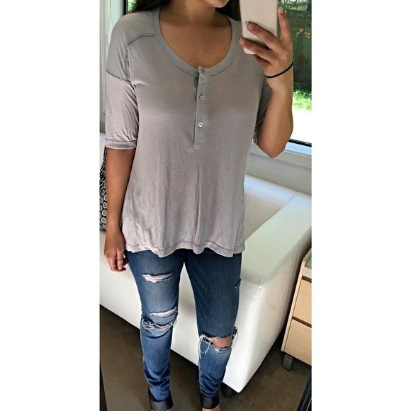 """Flowy Light Gray Henley Brand new without tags. A remix of the classic Henley top. Short sleeve, flowy and has a high/low hem. Soft material that features small ribbed detail. Three functioning buttons in the front. True to size. From a boutique brand.   •Made in the USA  •50% polyester, 50% rayon •Size Medium: 19"""" across bust, 24"""" front length, 27.5"""" back length   Price firm unless bundled, no trades. Please use the """"buy now"""" or """"add to bundle"""" features to purchase. Tops Tees - Short Sleeve"""