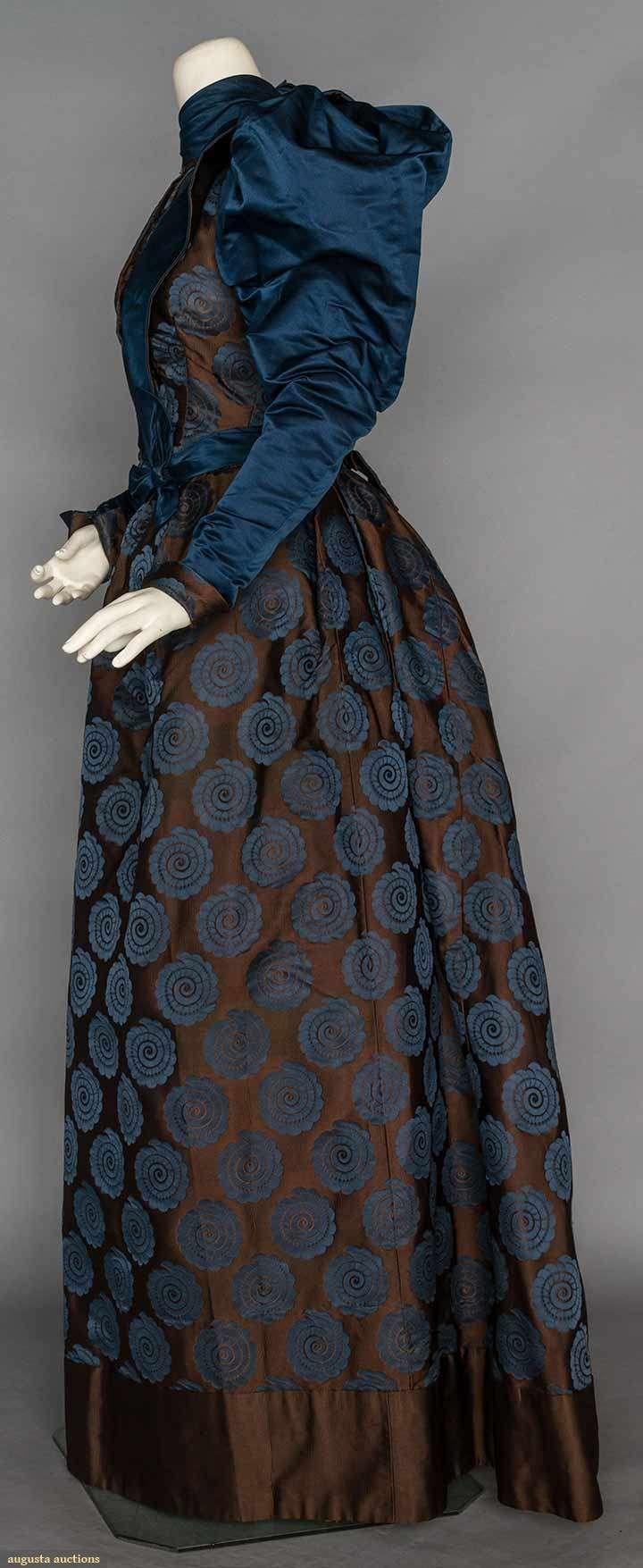 SILK BROCADE AFTERNOON DRESS, c. 1895. 2-piece of brown satin brocade w/ blue spiral rondels, blue satin high collar, lapels & gigot sleeves. Sideway