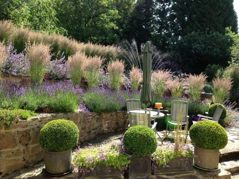Stützmauer im Garten für einen terrassierten Hang mit Gräsern ...