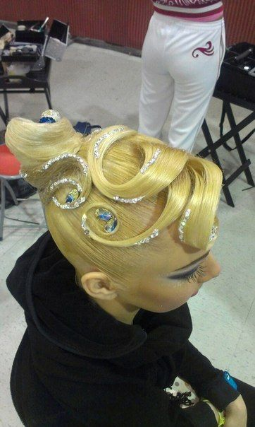 High swirl bun with bang swoop designs and stones. Good hairstyle for standard, but can be worn for latin as well. Visit http://ballroomguide.com/comp/hair_make_up.html for more hair and makeup info