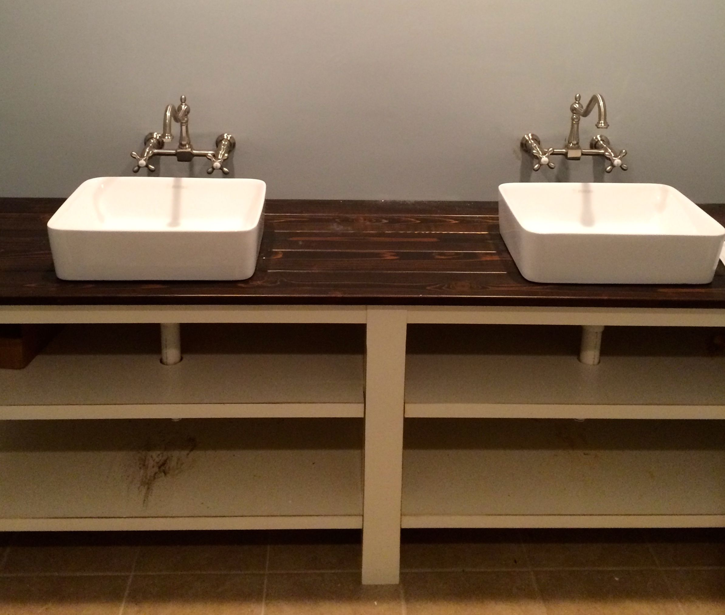 A bathroom vanity made out of a stained cedar plank countertop and open shelving underneath