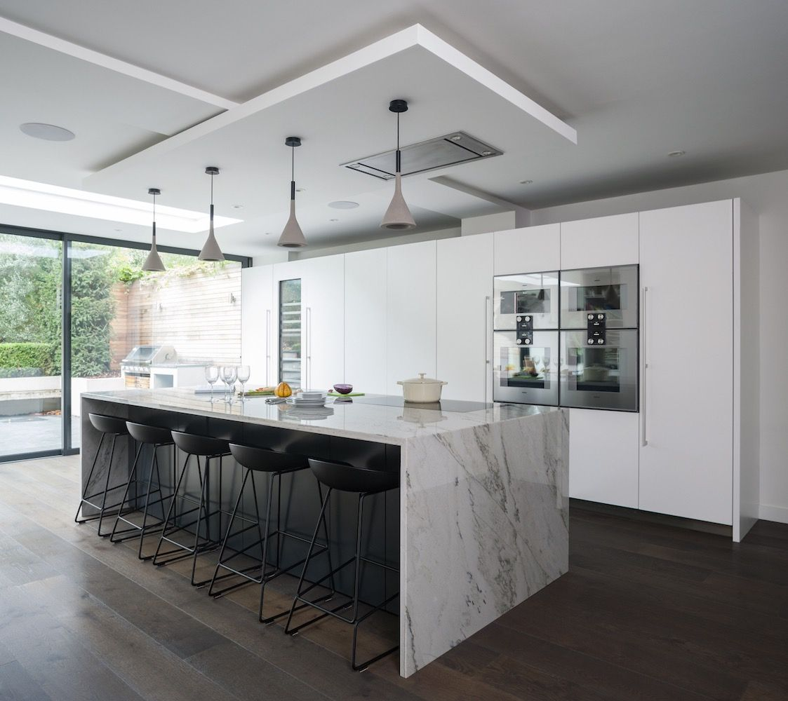 Modern Kitchen With White Waterfall Island Countertop And Black