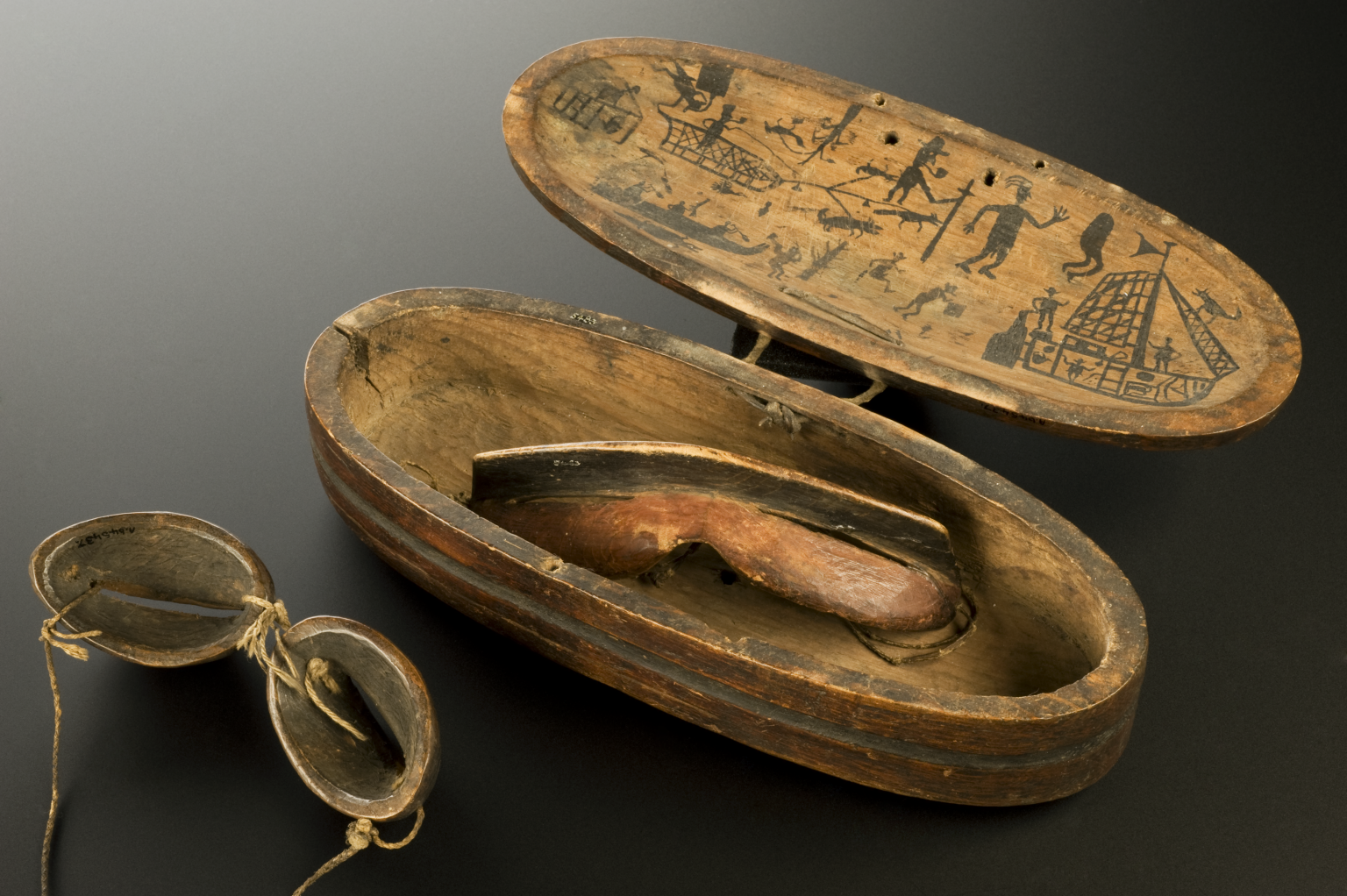 """""""Wooden snow goggles and case, Inuit, North America, 1801-1900: Snow blindness is caused by sunlight reflecting off white snow and ice. This painful condition causes temporary loss of vision. The Inuit people in North America wore goggles to shield their eyes from such glare. These goggles are made from pine and rawhide. Slits in the rawhide eye pieces let the wearer see. They are kept in a wooden case decorated with hunting scenes."""""""